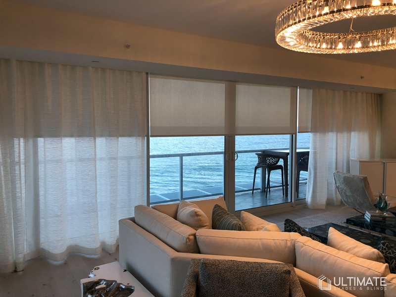 drapery with blinds in living room with ocean view